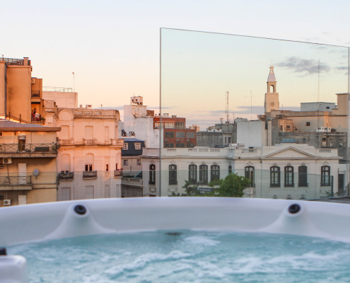 A rooftop jacuzzi at sunset with views over the nearby town