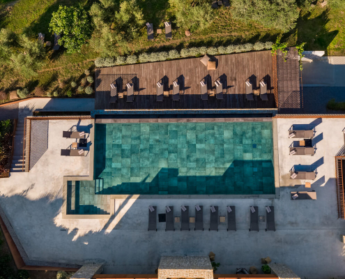 A drone view of a large turquoise infinity pool and its surrounding green trees and gardens and handful of sun loungers